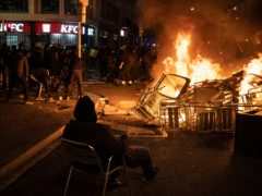 A man sits on a chair in front of a burning barricade as protesters collect objects during a protest condemning the arrest of rapper Pablo Hasel (AP)