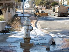 Water trickles from a fire hydrant while City of Austin Water Utility workers repair a broken water main near 11th and Red River streets in Austin, Texas (Jay Janner/Austin American-Statesman via AP)