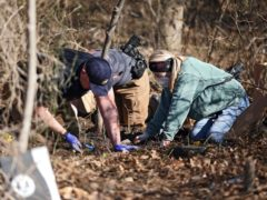 Investigators search through dirt at the scene where skeletal remains were found (Mike Simons/AP)