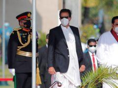 Pakistan prime minister Imran Khan, centre, stands with Sri Lankan premier Mahinda Rajapaksa (Eranga Jayawardena/AP)