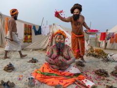 A Hindu Holy man prays as others shower flower petals on him (Rajesh Kumar Singh/AP)