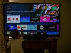 A child touches a TV screen displaying OTT streaming apps at his home in New Delhi, India (Altaf Qadri/AP)