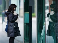 A woman wearing a face mask to help curb the spread of the coronavirus in Tokyo (AP)