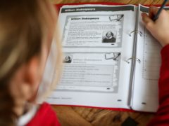 A nine year old school girl studies her homework folder following the final day of school following the Government announcement that all schools in England will close on Friday due to the Coronavirus pandemic.
