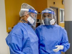 Health workers wearing full personal protective equipment (PA)