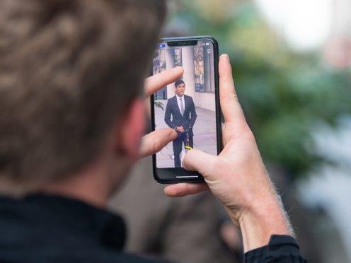A man takes a photo of Chancellor Rishi Sunak (Dominic Lipinski/PA)