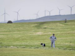 A man walking his dog near Whitehaven in Cumbria where plans for a coal mine have caused controversy (Danny Lawson/PA)
