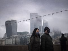 A couple wearing face masks walk past City of London skyscrapers (Victoria Jones/PA)