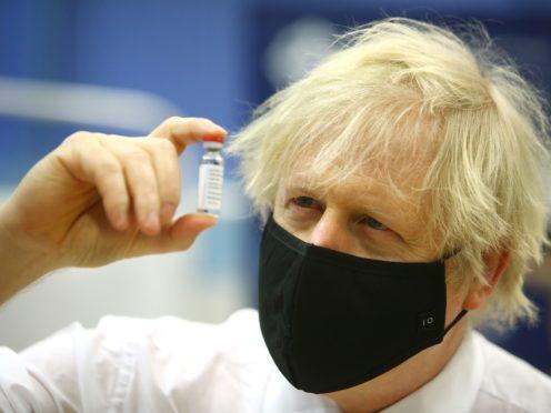 Boris Johnson holding a vial of the Oxford/AstraZeneca Covid-19 vaccine (PA)