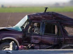 Law enforcement officers sort evidence and debris at the scene of a deadly crash in Holtville, California (Gregory Bull/AP)