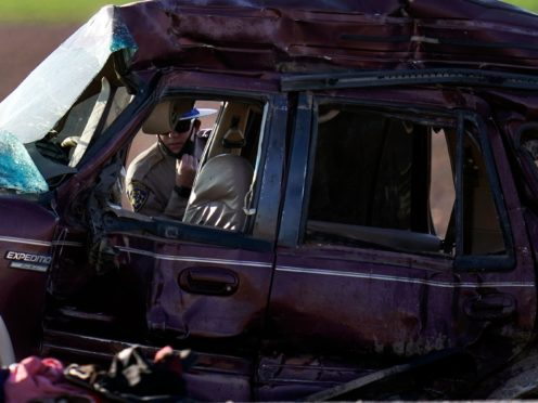 A California Highway Patrol officer examines the scene of a deadly crash in Holtville, California (Gregory Bull/AP)
