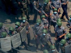 Policemen and soldiers armed with guns and slingshots advance towards anti-coup protesters in Mandalay, Myanmar, Wednesday, March 3, 2021. Demonstrators in Myanmar took to the streets again on Wednesday to protest last month's seizure of power by the military. (AP Photo)