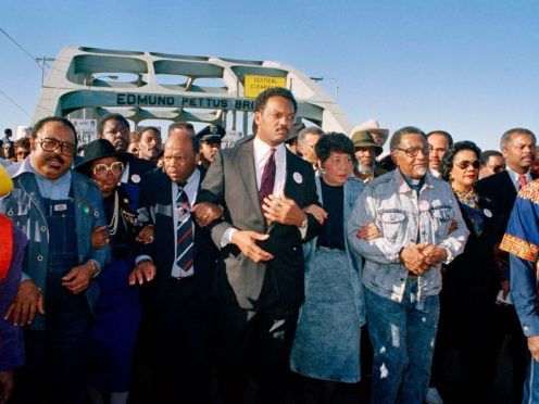 Civil rights figures lead marchers across the Edmund Pettus Bridge during the recreation of the 1965 Selma to Montgomery march in 1990 (AP)