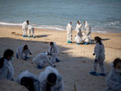 Israeli soldiers wearing protective suits clean tar from an Israeli beach after an oil spill in the Mediterranean Sea (Ariel Schalit/AP)