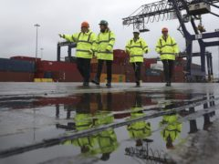 Prime Minister Boris Johnson and Chancellor of the Exchequer, Rishi Sunak are reflectd in a puddle as they walk past shipping containers during a visit to Teesport in Middlesbrough (Scott Heppell/PA)