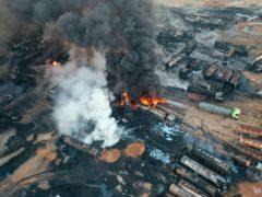 People work to extinguish burning oil tanker trucks after a suspected missile strike (Syrian Civil Defence White Helmets via AP)
