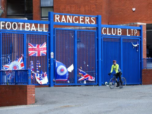 A cyclist stops outside the gates of the Ibrox Stadium (PA)