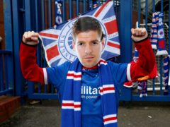 A Rangers fan wears a Steven Gerrard mask outside Ibrox (Robert Perry/PA)