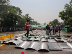 An anti-coup protester sprays water on metal-makeshift shields to prevent from heat in hot-sunny weather in Yangon, Myanmar (AP)