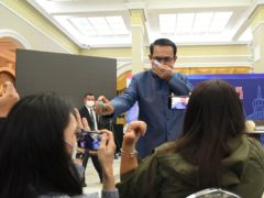 Thailand's prime minister Prayuth Chan-ocha sprays alcohol mist on a front row of reporters (AP)