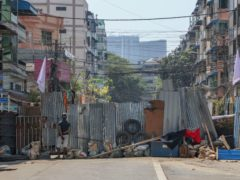 A vigilante stands behind makeshift barricade in Yangon, Myanmar (STR/AP)