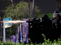 Sparks fly from the barrel of a gun used by riot police to disperse protesters (AP/Sakchai Lalit)
