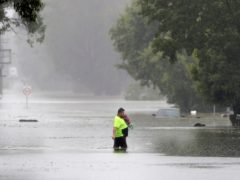 A man walks across a flooded street in Windsor, north-west of Sydney, New South Wales (Rick Rycroft/AP)
