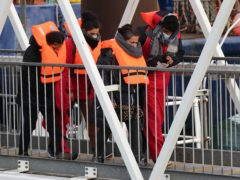 A group of people thought to be migrants are brought in to Dover, Kent, by Border Force officers following a small boat incident in the Channel (PA)