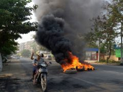 Anti-coup protesters pass burning tires in Yangon (AP)