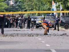Police officers inspect the scene after a suicide bombing outside a church in Makassar, Indonesia (Masyudi S Firmansyah/AP)
