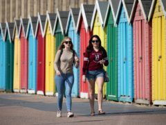 People make their way past beach huts on the sea front on Boscombe beach (Andrew Matthews/PA)