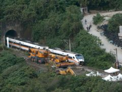 Rescue workers remove a part of the derailed train near Taroko Gorge in Hualien, Taiwan (Chiang Ying-ying/AP)