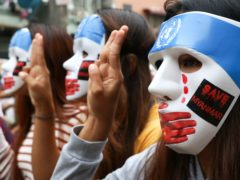 Young demonstrators flash the three-fingered symbol of resistance during an anti-coup mask strike in Yangon (AP)