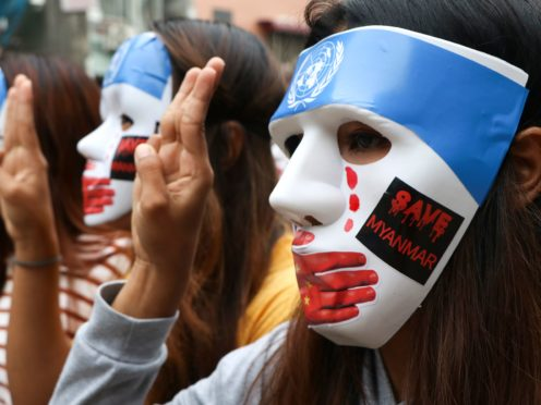Young demonstrators flash the three-fingered symbol of resistance during an anti-coup mask strike in Yangon, Myanmar (AP Photo)