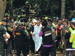 Rescuers help Phra Manas walk out from the Tham Phra Sai Ngam cave (AP)