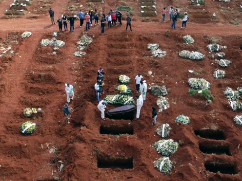 Cemetery workers wearing protective gear lower the coffin of a person who died from complications related to Covid-19 into a gravesite in Brazil (AP/Andre Penner)