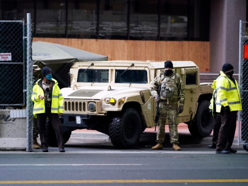 A National Guard soldier, centre, stands guard with deputies at the restricted vehicle entrance of the Hennepin County Government Centre (Jim Mone/AP)