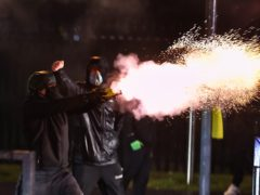 Youths fire fireworks at the PSNI on the Springfield road, during further unrest in Belfast (Liam McBurney/PA)