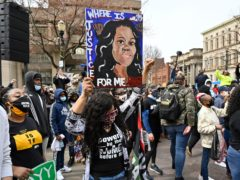 A protester holds up a painting of Breonna Taylor during a rally on the one year anniversary of her death at Jefferson Square Park in Louisville (Timothy D Easley/AP)