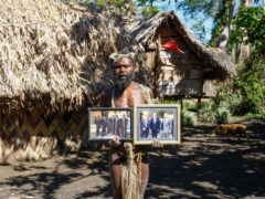 Albi Nagia poses with photographs of Prince Philip in Yakel, Tanna island, Vanuatu in May 31 2015 (AP Photo/Nick Perry, File)