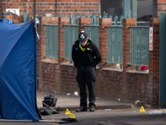 A police officer inspects the scene at an industrial premises on Western Road near Birmingham's City Hospital (Jacob King/PA)