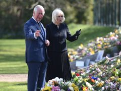 The Prince of Wales and the Duchess of Cornwall view flowers left in tribute to the Duke of Edinburgh (Jeremy Selwyn/Evening Standard/PA)