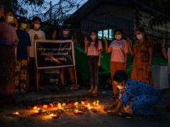 A woman lights a candle while others flash the three-fingered sign of resistance during a candlelight vigil to remember those who died in the military junta's violent response to anti-coup demonstrations in Yangon, Myanmar (AP)