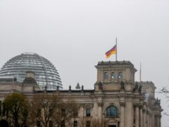 The German flag on top of the Reichstag building flies at half-mast (Christoph Soeder/dpa via AP)