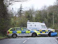 PSNI vehicles block a road near the scene (Niall Carson/PA)