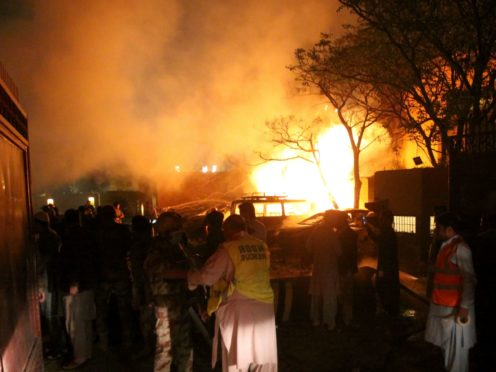 A police officer and rescue workers arrive at the site of a bomb blast in Quetta (Arshad Butt/AP)