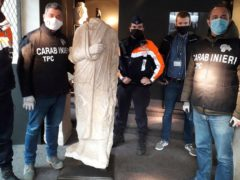 Carabinieri officers of the art squad's archaeological unit pose with a headless Roman statue wearing a draped toga in Brussels (Carabinieri via AP)