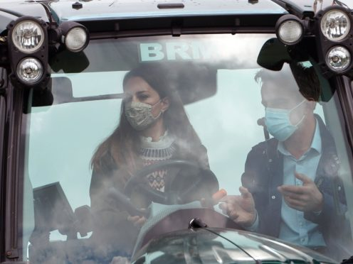 Farmer Stewart Chapman gives the Duchess of Cambridge instructions on how to drive a tractor during her visit to Manor Farm in Little Stainton, Durham (Owen Humphreys/PA)
