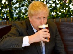 Prime Minister Boris Johnson sips a pint in a beer garden (PA)