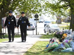 Police Community Support Officers walk past floral tributes in a park in Aylesham village close to the scene in Snowdown, Kent, where the body of PCSO Julia James was found (PA)